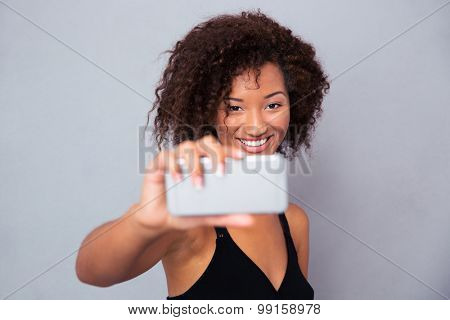 Portrait of a happy afro american woman making selfie photo on smartphone over gray background