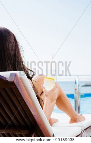 Portrait of a young woman lying on deckchair with cocktail outdoors