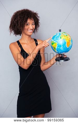 Portrait of a happy african woman holding globe over gray background
