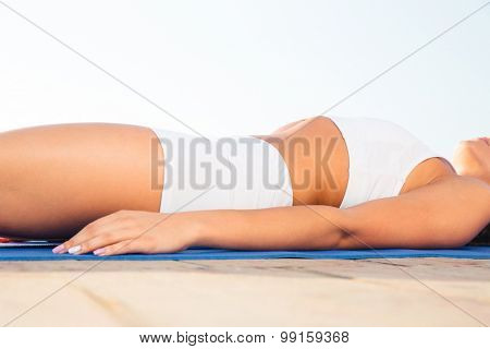 Closeup portrait of a woman`s body lying on yoga mat
