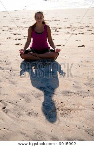 Woman doing yoga on beach.