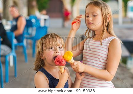 Portrait of two adorable kids eating colorful ice cream outdoors