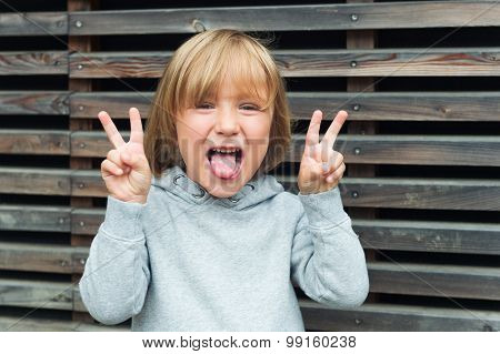 Close up portrait of a funny little boy, wearing grey sweatshirt