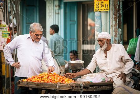 Indian man buying tomatoes n the street of Old Delhi