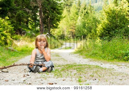 Portrait of a cute little boy hiking in a forest, sitting on ground, holding a stick