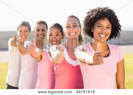 Portrait of smiling women wearing pink for breast cancer and doing thumbs up in parkland
