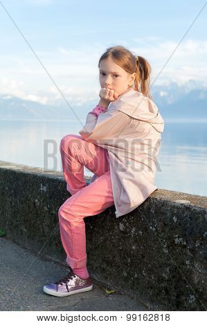 Cute little girl resting by the lake, wearing pink coat and trousers