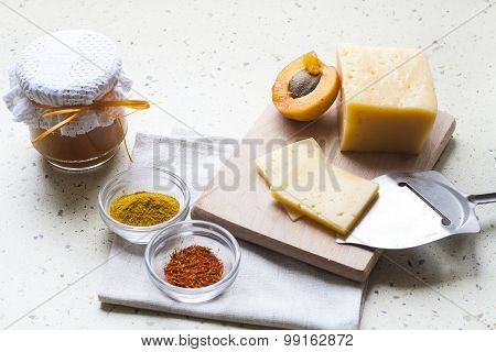 Solid sliced cheese with apricot curry in ceramic ware, spices and fresh apricots, selective focus