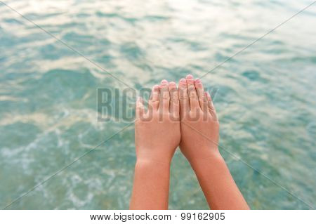 Kids hands against beautiful turquoise see. Kid is ready to  dive into the water