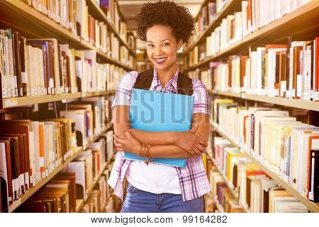Casual young woman with folder in office against close up of a bookshelf