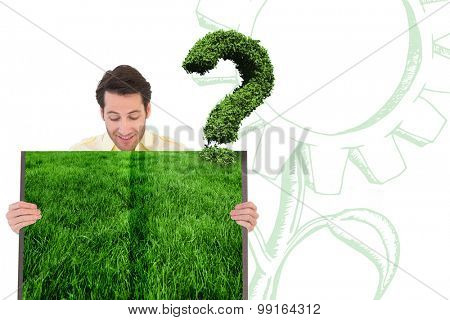 Man holding lawn book against question mark made of leaves