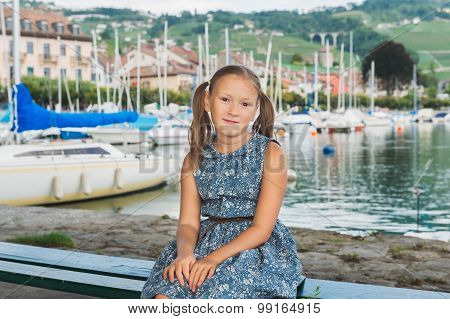Fashion portrait of a cute little girl sitting on a bench by the lake, wearing blue dress