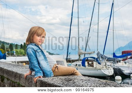 Fashion portrait of a cute little blond boy sitting by the lake, wearing denim shirt and beige trous