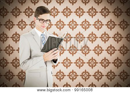 Geeky businessman reading black book against background