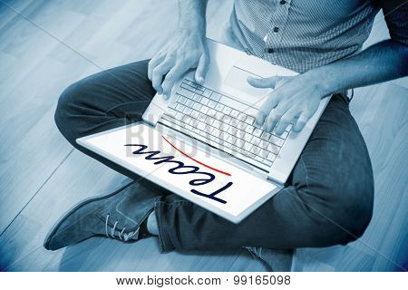 The word team against young creative businessman working on laptop