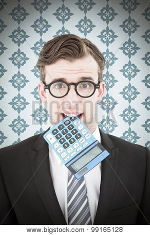 Geeky businessman biting calculator against blue background