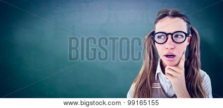 Female geeky hipster looking confused against green chalkboard