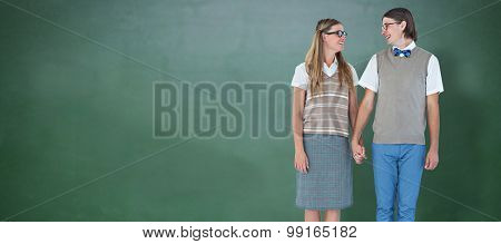 Geeky hipster couple holding hands and looking at each other against green chalkboard