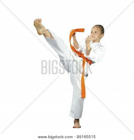 Sportswoman with an orange belt is beating mae-geri