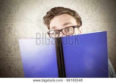Geeky student reading a book against elegant patterned wallpaper in neutral tones