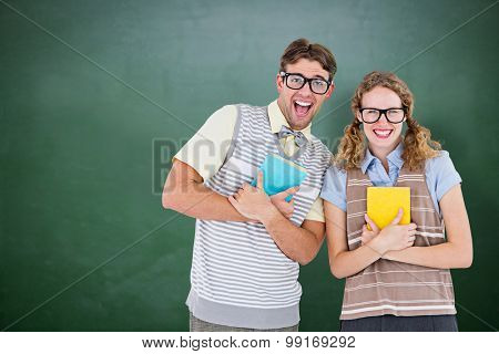 geeky hipster couple holding books and smiling at camera against green chalkboard