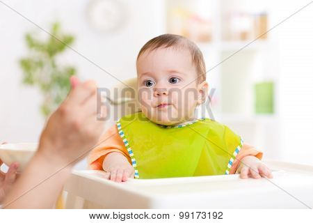Mom feeding baby with spoon