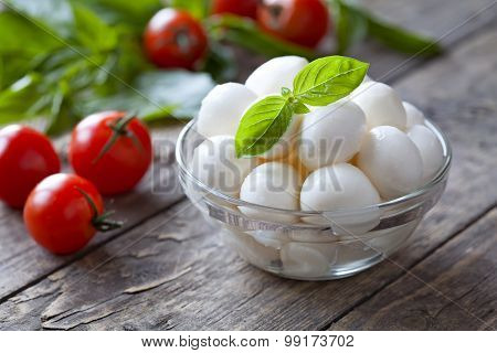 Traditional italian mozzarella cheese in glass bowl with basil and tomatoes caprese on rustic wooden