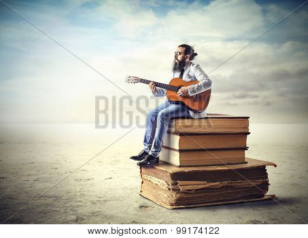 Man playing the guitar while sitting on a pile of books