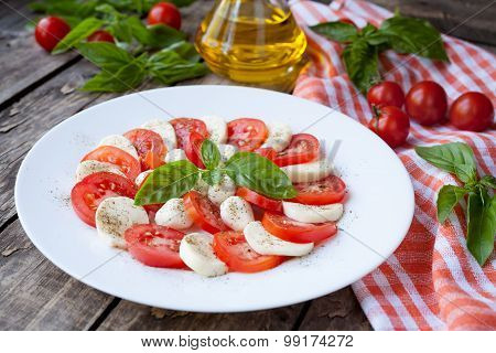 Healthy traditional Italian organic vegetarian caprese antipasti salad with sliced mozzarella tomato