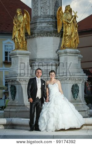 Newlyweds Standing In Front Of Fountain