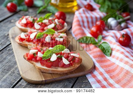 Homemade traditional italian bruschetta antipasti with roasted baguette, tomatoes, basil and mozzare