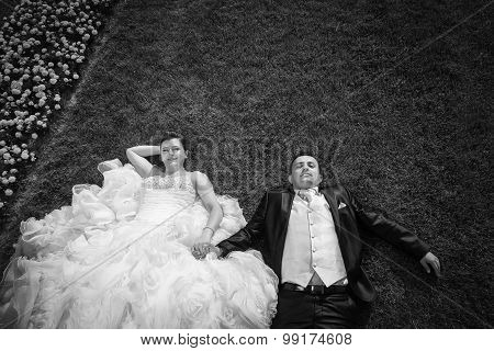 Bride And Groom Holding Hands On Lawn With Flowers Bw