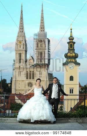 Bride And Groom Posing In Front Of Church