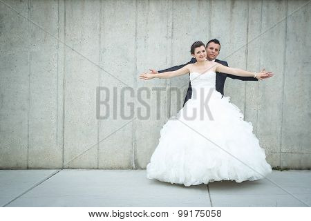 Bride And Groom Spreading Arms