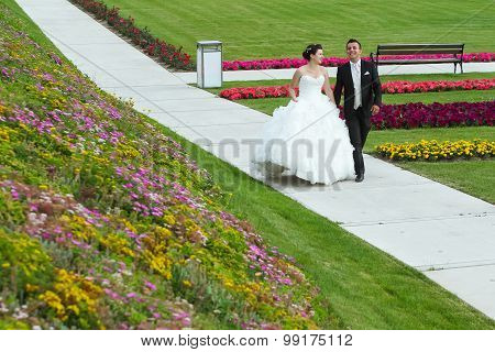 Bride And Groom Walking On Pathway