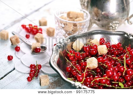 Fresh red currants with sugar on table close up
