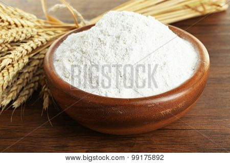 Whole flour in bowl with wheat ears on wooden table, closeup