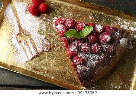 Cake with Chocolate Glaze and raspberries on tray on wooden background