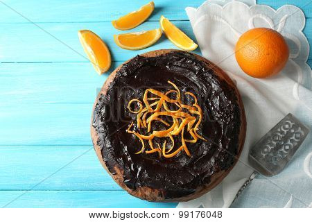 Cake with Chocolate Glaze and orange on color wooden background