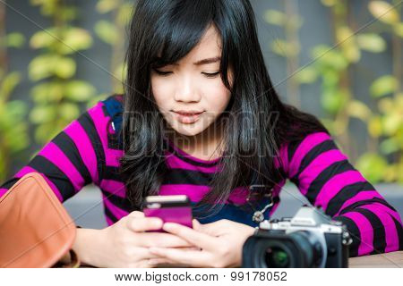 Young Photographer Woman Using On Mobile Phone In Cafe