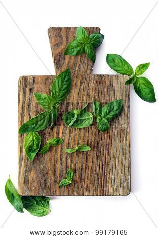 Green fresh basil with cutting board isolated in white