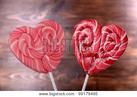 Bright lollipops in shape of heart on wooden background