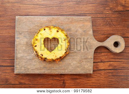 Pineapple slice with cut in shape of heart on wooden background