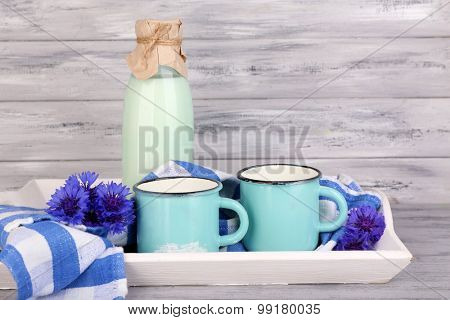 Bottles and cups of milk with cornflowers on wooden tray