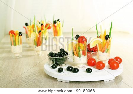 Snack of vegetables in glassware on wooden table on curtains background