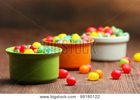 Colorful candies in bowls on table on wooden background
