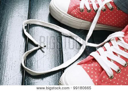 Female feet in gum shoes on color wooden background
