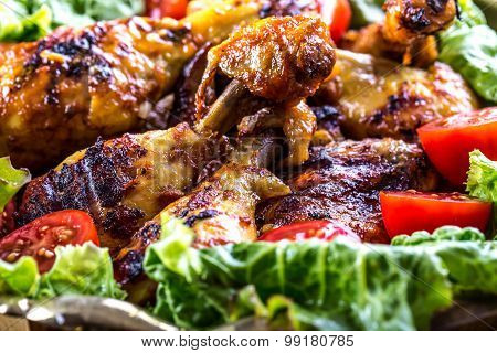 Grilling. Grilled chicken. Grilled chicken legs. Grilled chicken legs, lettuce and cherry tomatoes.