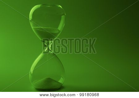 Hourglass on green background