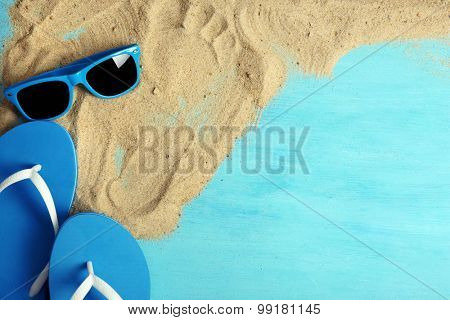 Flip flops and sunglasses with sand on wooden background